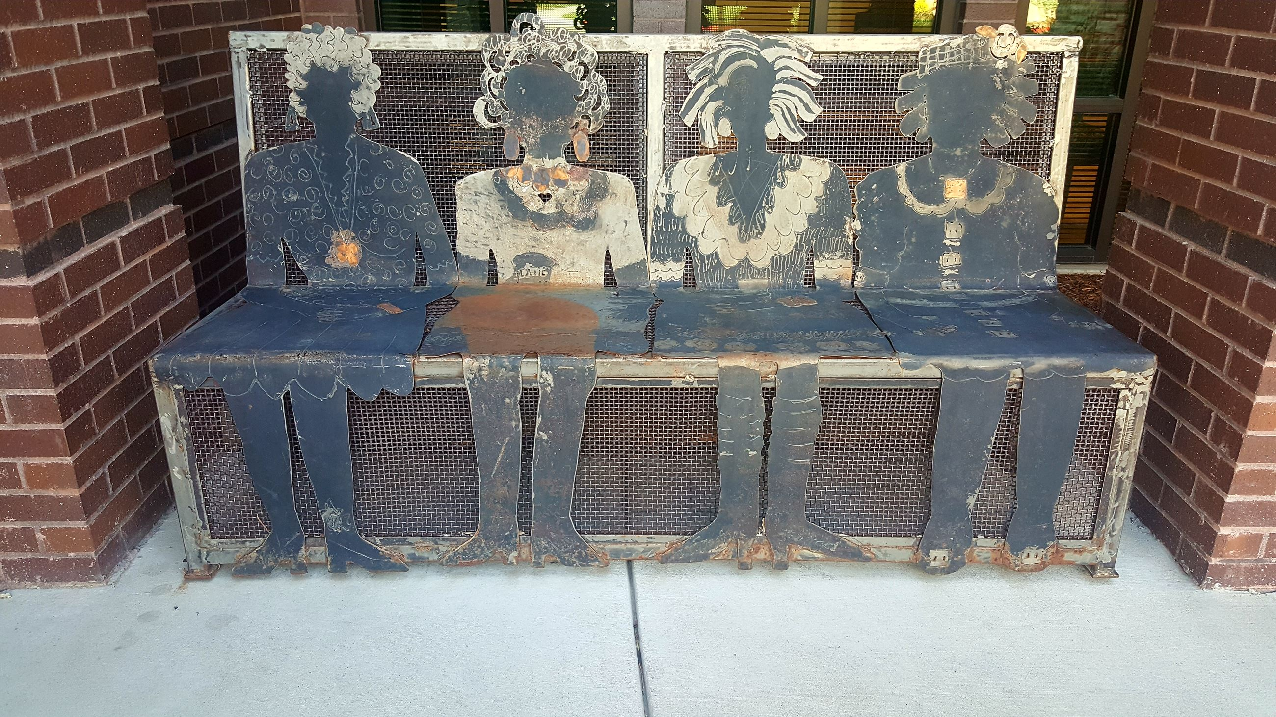 Bench with metal cutouts that look like women.