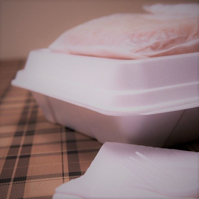 A white Styrofoam takeout container and napkins on a brown tablecloth.