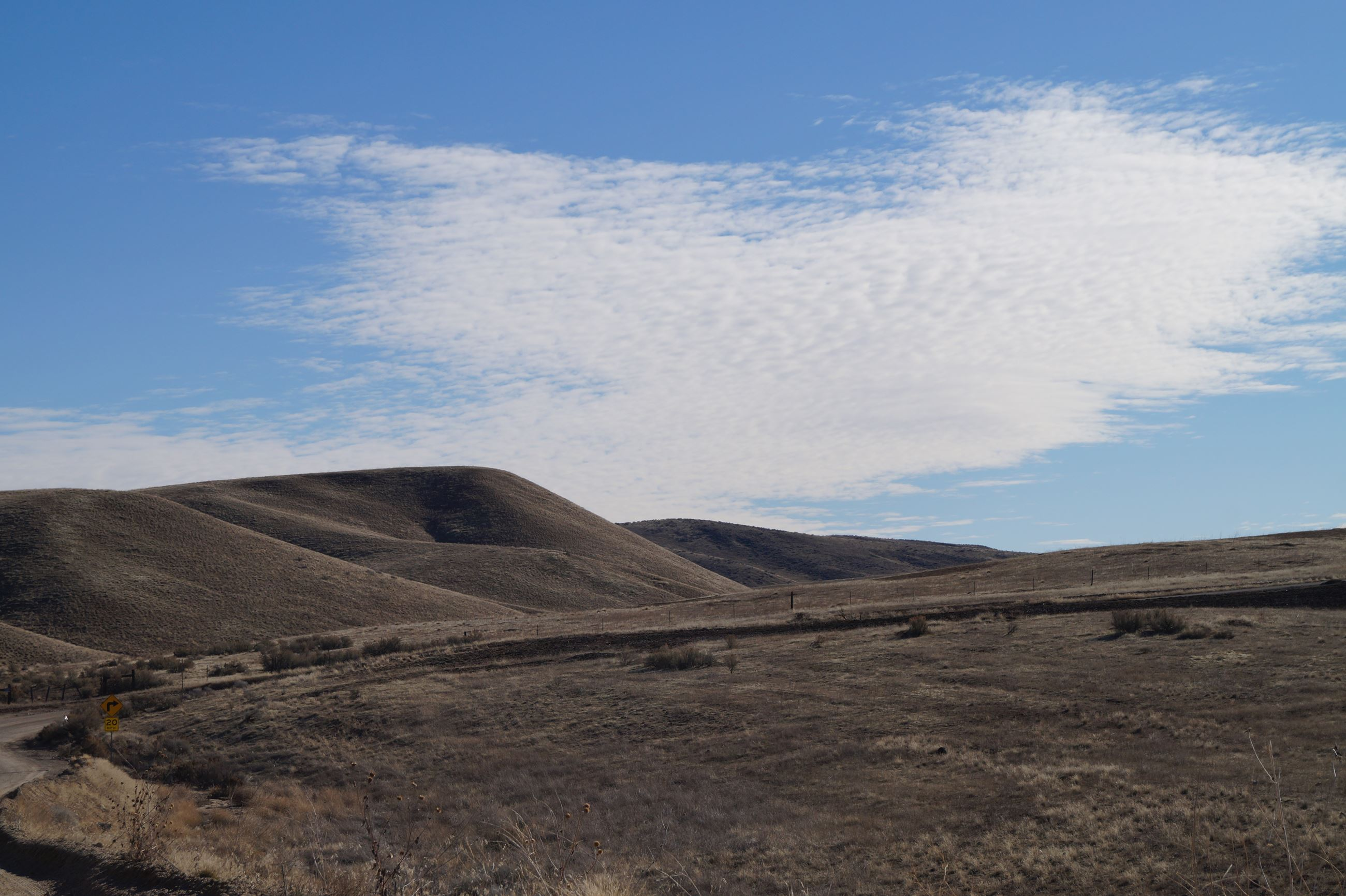 A photo of the Eagle Foothills with blue sky and clouds.