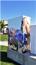 Electrical box with an image of a cowboy on a bull with horses and a crowd in the background.