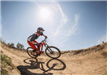 Bmx Racer Takes a Tight Angled Curve Along a Dirt Path