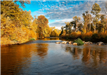Serene River Surrounded by Fall-Colored Trees