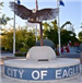 Sculpture of an Eagle on a Post with Spread Wings Above a Platform That Reads City of Eagle