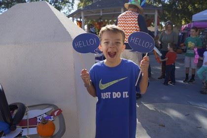 Boy with Two Text Balloon Signs That Say Hello