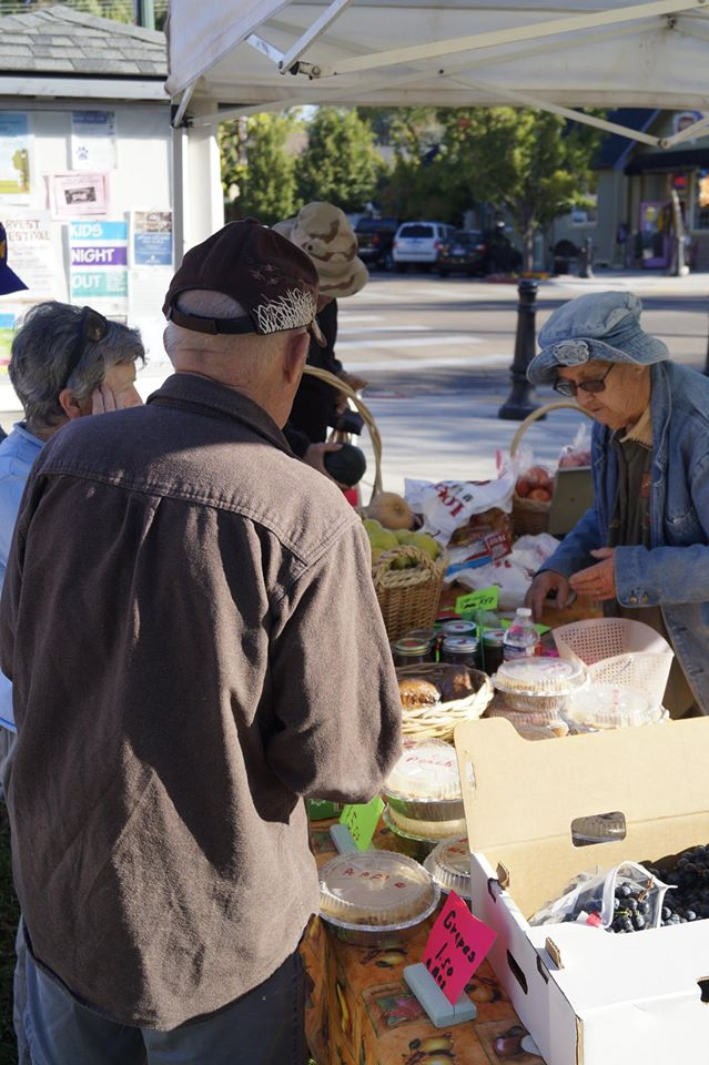 People Looking at Baked Goods for Sale