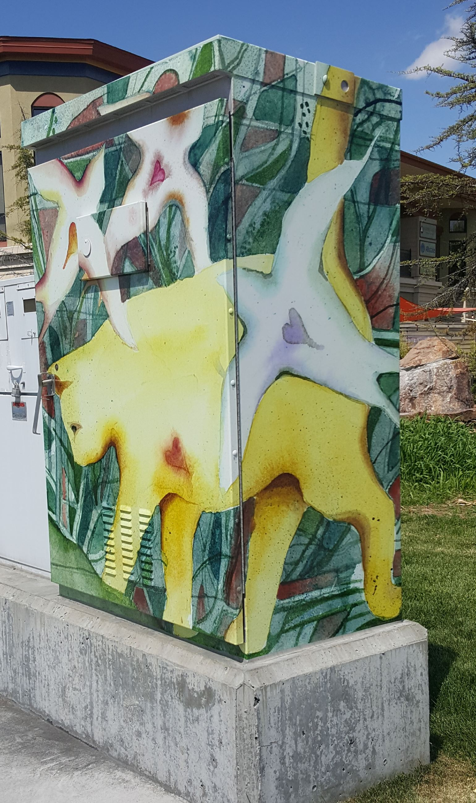 Electrical box with images of a yellow cat and white birds on a green background.