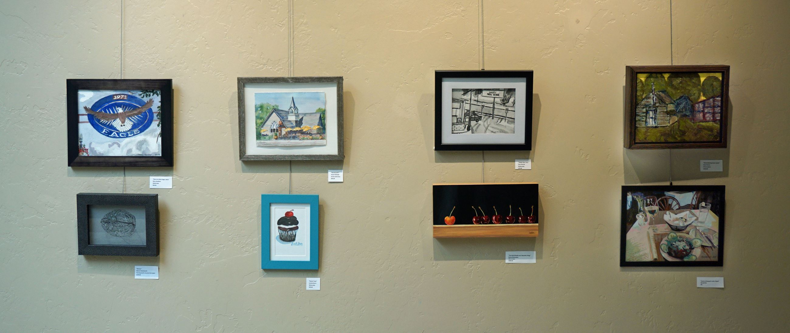 Image shows 8 small paintings hanging in front of a wall.
