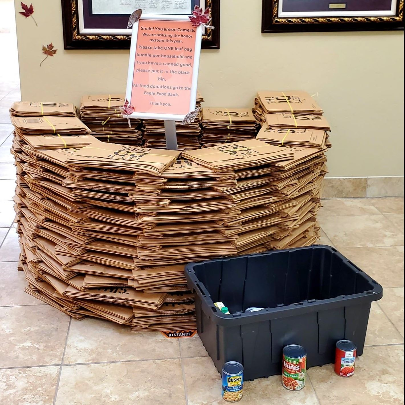 A tall stack of paper leaf bags with a canned food donation box in front of it.